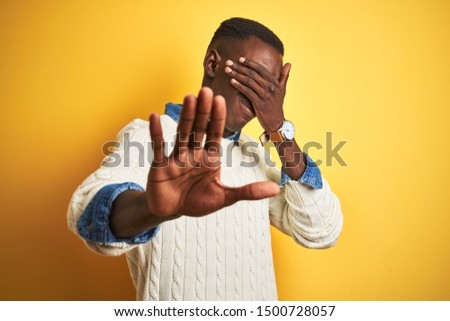 African american man wearing denim shirt and white sweater over isolated yellow background covering eyes with hands and doing stop gesture with sad and fear expression. Embarrassed and negative