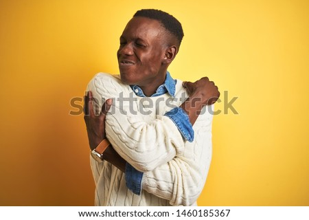 African american man wearing denim shirt and white sweater over isolated yellow background Hugging oneself happy and positive, smiling confident. Self love and self care