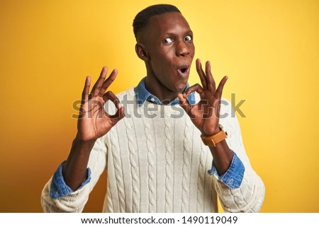 African american man wearing denim shirt and white sweater over isolated yellow background looking surprised and shocked doing ok approval symbol with fingers. Crazy expression
