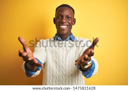 African american man wearing denim shirt and white sweater over isolated yellow background smiling cheerful offering hands giving assistance and acceptance.