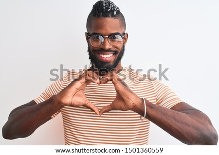 African american man wearing striped t-shirt and glasses over isolated white background smiling in love showing heart symbol and shape with hands. Romantic concept.