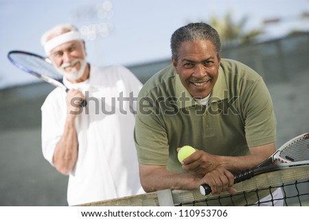 African American man with a friend playing tennis
