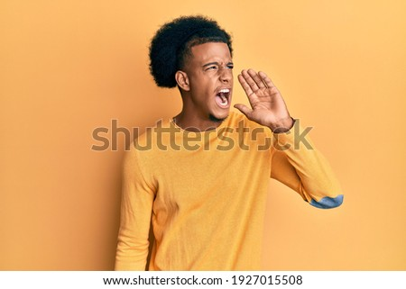 African american man with afro hair wearing casual clothes shouting and screaming loud to side with hand on mouth. communication concept.  Foto stock ©