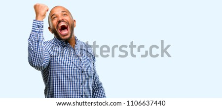 African american man with beard happy and excited expressing winning gesture. Successful and celebrating victory, triumphant isolated over blue background