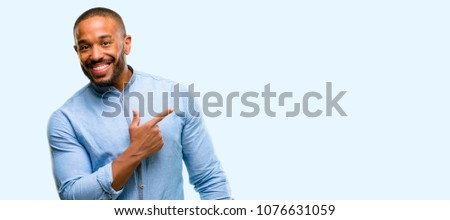 African american man with beard pointing away side with finger isolated over blue background