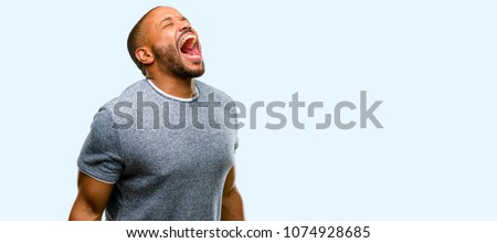 African american man with beard stressful, terrified in panic, shouting exasperated and frustrated. Unpleasant gesture. Annoying work drives me crazy isolated over blue background