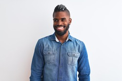 African american man with braids wearing denim shirt over isolated white background looking away to side with smile on face, natural expression. Laughing confident.