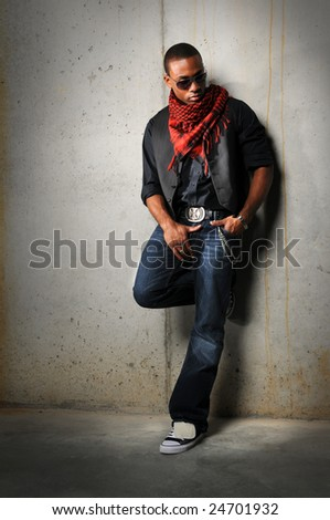 African American man with red scarf standing against a concrete wall