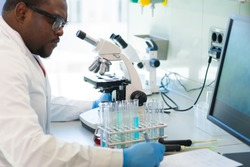 African-american man working in lab. Scientist doctor making medical research. Laboratory tools: microscope, test tubes, equipment. Biotechnology, chemistry, science, experiments and healthcare.