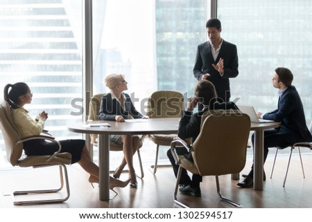 African american manager speaking at board team meeting, black business coach giving new business plan presentation reporting talking to diverse executive group at modern office briefing in boardroom