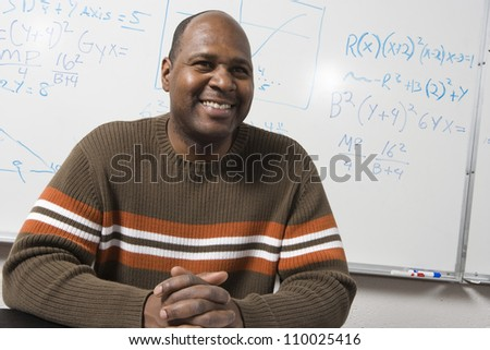 African American math professor sitting in front of whiteboard