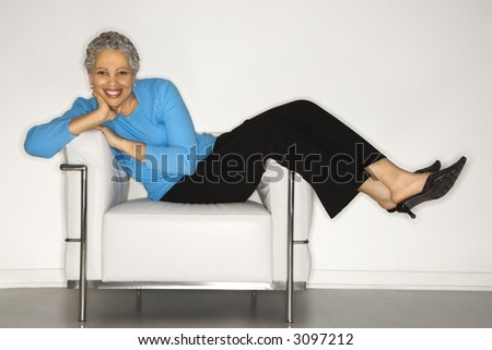 stock photo : African American mature adult female lying back on chair.