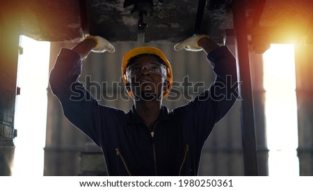 african american Mechanic repairing big heavy industry machine . black engineer maintenance machinery in Large Industrial Factory. young worker checking or inspection working machine at site indoor Photo stock ©