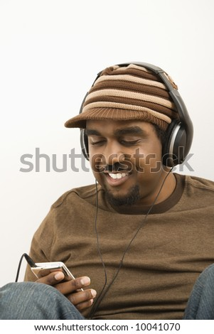 African-American mid-adult man wearing hat and listening to mp3 player.