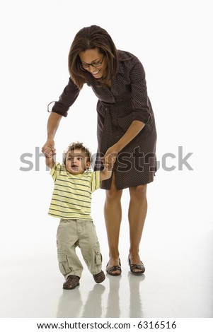 African American mid adult mother holding arms of toddler son learning to walk.
