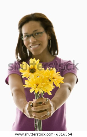 African American mid adult woman wearing glasses holding bouquet of flowers towards viewer.