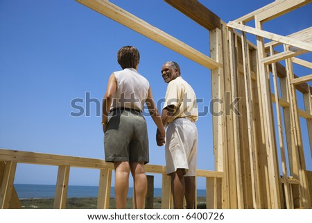 African American middle aged couple holding hands in new home construction at beach.