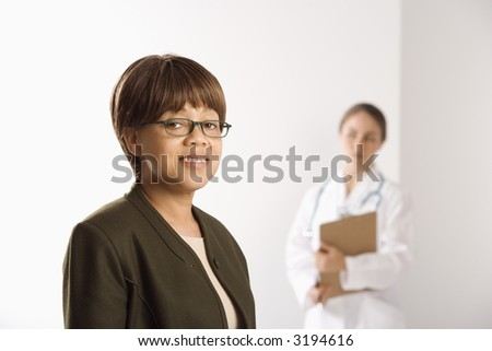African American middle-aged female patient woman smiling looking at viewer with Caucasian mid-adult female doctor standing in background.