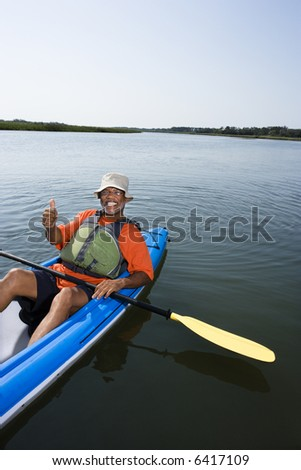 African American middle-aged man smiling and giving thumbs up gesure in kayak.