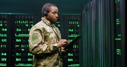 African American military man in uniform and headset working in servers room, tapping on tablet device and speaking in mic. Work with secret information in army. Digital data defence concept.