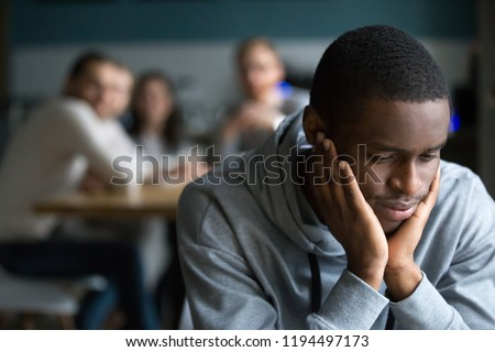 African American millennial guy feel lonely sitting alone in café, offended black student avoid talking to friends having misunderstanding, young man outcast suffer from racial discrimination