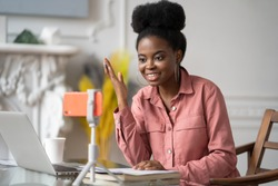 African American millennial woman with afro hairstyle remote studying, working online on laptop, chatting with friends via video call on smartphone on tripod. Blogger influencer recording video blog.