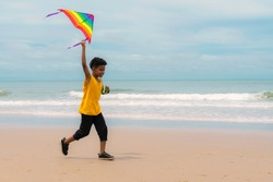 African American mixed race boy in yellow tank top run on the beach with rainbow color kite under blue sky with copy space. Concept of childhood, friendship, summer leisure and vacation