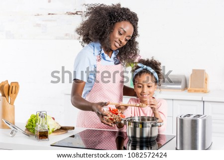 african american mom and daughter cooking on electric stove together
