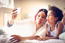 African American mother and daughter taking self picture together in bed. Space for copy.