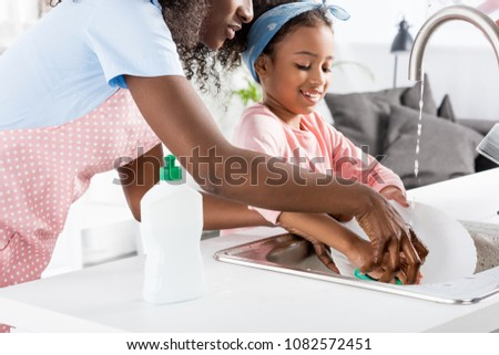 african american mother and daughter washing dishes with detergent on kitchen
