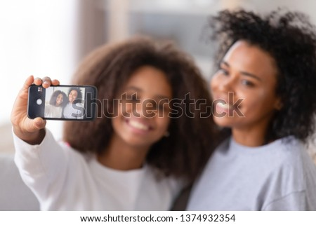 African American mother and teenage daughter taking selfie, smiling teen girl holding phone, happy mum posing for photo with child, close up mobile device, family having fun together with gadget