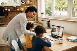 African American mother assisting her children who are learning online and having video call with their teacher over a laptop at home.