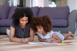 African American mother coloring with daughter, lying on warm floor in living room at home, smiling family spending free time, weekend together, woman drawing colored pencils with pretty girl