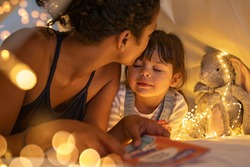 African american mother kissing her daughter on forehead while lying on bed in illuminated tent. Mother putting daughter to sleep in cozy hut after reading a fairy tale in tent. Mom kissing cute girl.