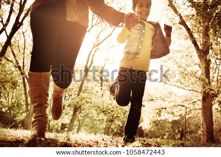 African American mother running trough park with her daughter and holding hands. #1058472443