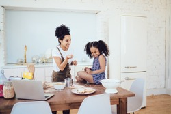 African American mother with flour in hand laughing and playing with child while little girl sitting on table and squinting
