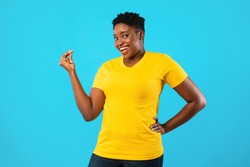 African American Oversized Woman Gesturing Clicking Fingers Standing Posing On Blue Background In Studio, Smiling To Camera. Finger Snap Gesture Concept