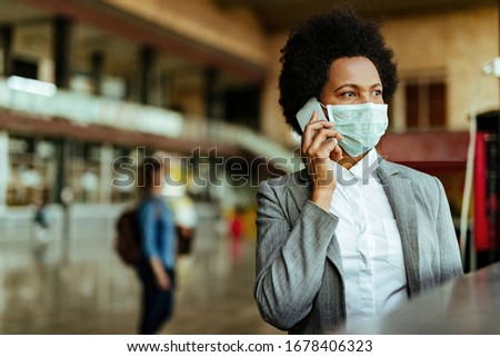 African American passenger communicating over cell phone while wearing face mask during virus epidemic at railroad station.