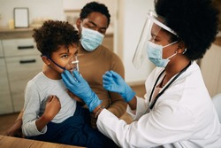 African American pediatrician using nebulizer during inhaling therapy of a small boy due to coronavirus pandemic.