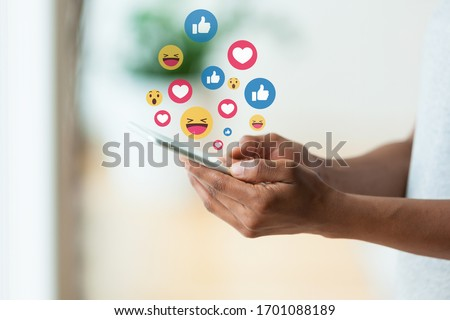 African american person holding a tactile mobile smartphone sending text messages emoji emoticon - Black people