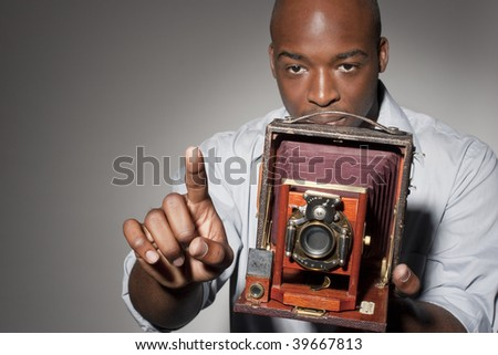African American photographer gesturing and holding an old-fashioned large format camera.