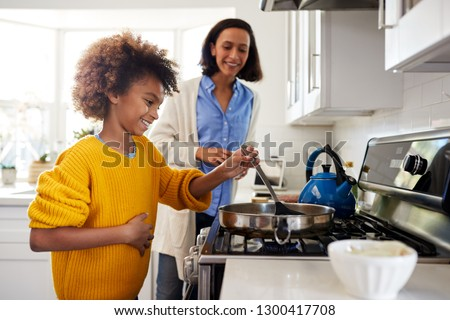 African American pre-teen girl standing at hob in the kitchen using spatula and frying pan, preparing food with her mother, side view