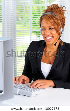 African American Pretty Female Call Center Agent Wearing A Telephone Headset Using A Computer In An Office