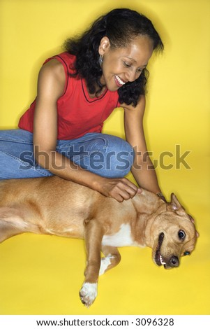 African American prime adult female petting dog.