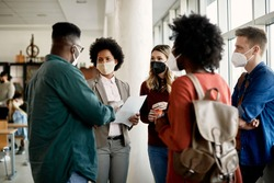 African American professor communicating with her students at university hallway. They are wearing face masks due to coronavirus pandemic.