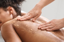 African american relaxed lady having skin scrubbing procedure at spa salon, closeup. Spa therapist applying exfoliating body mask on sleeping black woman back at luxury spa, body care concept