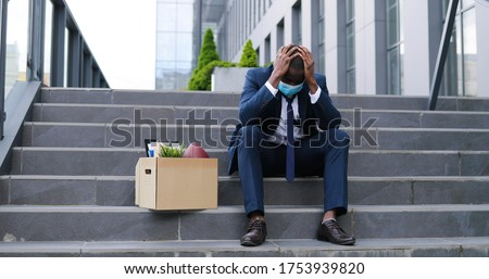 African American sad businessman in medical mask sitting on stairs outdoor with box of stuff as lost business. Male office worker in despair lost job. Unemployment rate growing due pandemic. Fired man