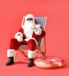African-American Santa Claus with cocktail sitting on sun lounger against color background