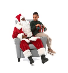 African-American Santa Claus with cute little boy on white background