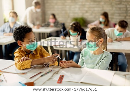 African American schoolboy spraying classmate's hands with disinfectant while wearing protective face masks on a class in the classroom.